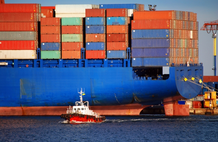 Giant Blue Container Ship and Small Red Tugboat
